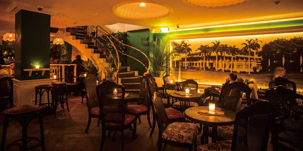 Vibrant Caribbean-themed bar with cane light fittings and potted plants, serving 250 types of rum.